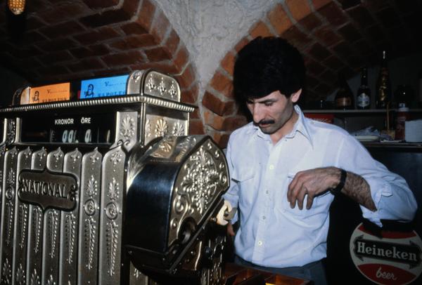 Dede tar betalt för en öl vid den gamla kassaapparaten.